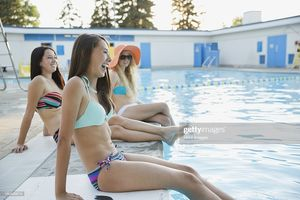 Teenage Girls Sitting By Swimming Pool..