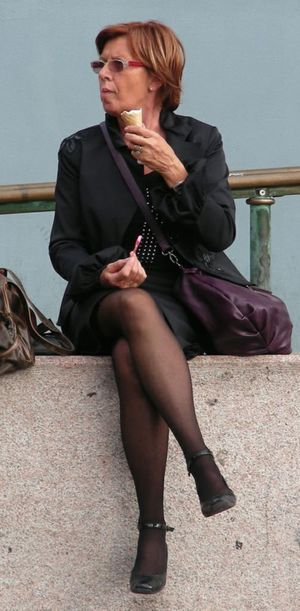 Mature Woman In Pantyhose Sits With..